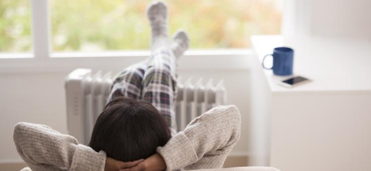 Banner Heizstrom. Frau sitzt gemütlich auf dem Sofa und hat die Füße auf ihren elektrischen Heizkörper gelegt.