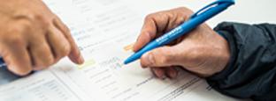 Nahaufnahme Hand mit Kugelschreiber füllt Formular aus