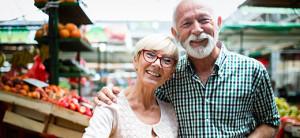 ein älteres Paar vor Ständen eines Wochenmarktes