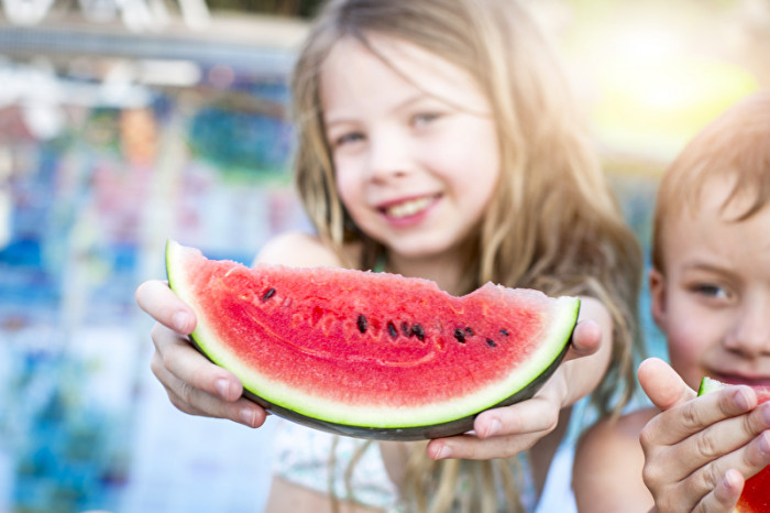 Kleines Mädchen streckt ein Stück Wassermelone entgegen