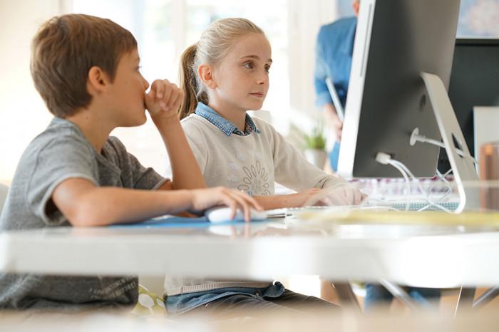 Junge und Mädchen arbeiten an einem Computer