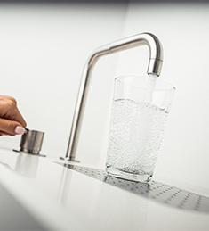 gefülltes Glas unter einem Wasserhahn